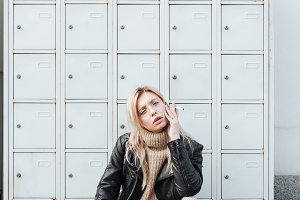 Serious young blonde lady sitting near safes.