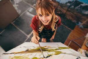 Smiling woman painter drawing