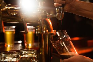 Close up of a bartender pouring beer