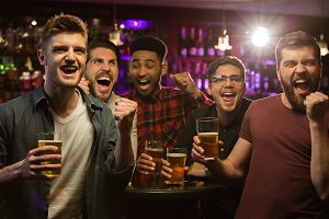 Four happy men holding beer mugs and gesturing
