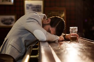 Drunk man sleeping on a pub counter