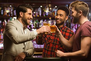 Happy smiling male friends clinking with beer mugs