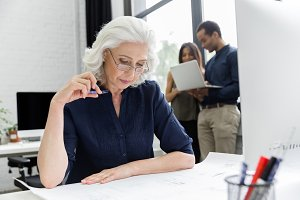 Mature businesswoman working with documents while sitting at her workplace