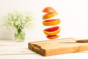 Sliced whole grapefruit flying above a wooden chopping board