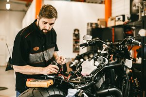 Confident young man repairing motorcycle in repair shop - electronics repair.