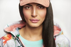 Pretty female model in casual jacket and cap