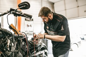 Motorcycle mechanic repairing electronics sports black bike.