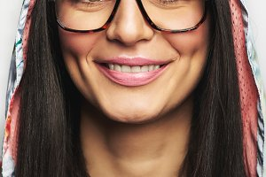 Smiling female face in glasses and hood