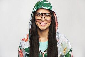Pretty cheerful female model posing in hood and glasses
