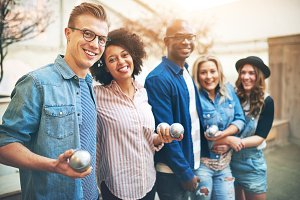 Multiracial group of friends standing together with petanque balls