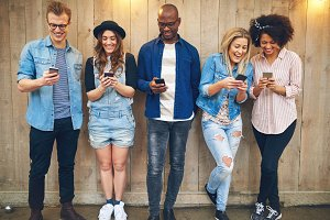 Group of multiracial friends browsing phones at wooden wall