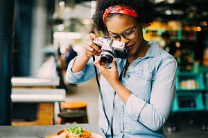 Young woman photographing her food on a cafe counter