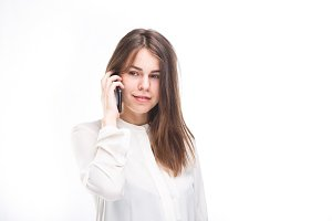 Beautiful young girl in a white shirt on white isolated background talking on a mobile phone. Smiles portrait to the waist