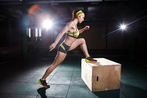Young, strong muscular girl jumps in the gym to the elevation. Leg training and cardio