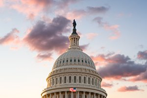 Flag flies in front of Capitol in DC at sunrise