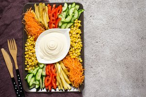 Homemade mayonnaise sauce And set of colorful vegetables. Russian salad goat in the garden. Top view with copy space