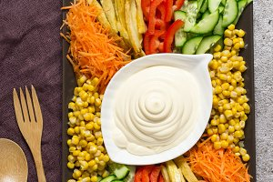 Homemade mayonnaise sauce. Dish with set of colorful vegetables. Russian salad goat in the garden. Top view