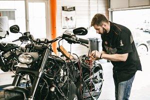 Professional motorcycle mechanic working in bike repair service.