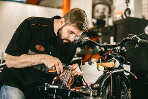 Professional motorcycle mechanic works with electronics, cuts wires.