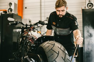 Handsome mechanic removing motorcycle wheel with special tools.