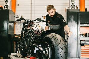 Mechanician changing motorcycle wheel in bike repair shop.