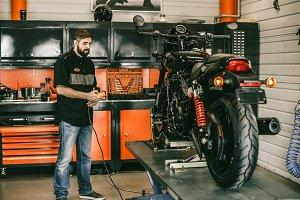 Professional moto mechanic raises a motorcycle on the lift.