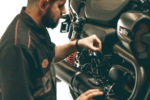 Professional bike mechanic checks the level of oil in the motorcycle.