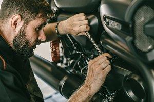 Closeup image of motorcycle mechanic repairing motorcycle in automobile store.