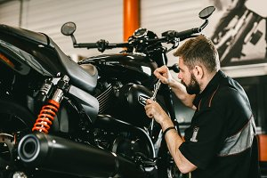 Professional mechanic working screwdriver and motorcycle repairs