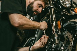 A professional mechanic unscrews the front wheel of a motorcycle.