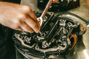 Closeup hands of motorcycle mechanic engine repair at service station