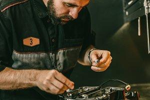 Motorcycle mechanic replacing glow plugs in bike engine