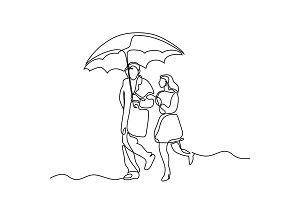 Couple walking under umbrella.