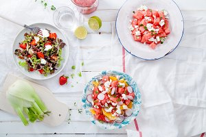 Variety of raw fresh summer salads with fruits and berries