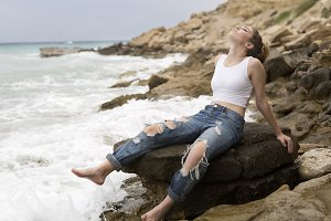 Teenage girl sitting on the rocks