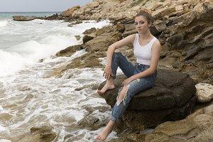 Teenage girl sitting on the rocks