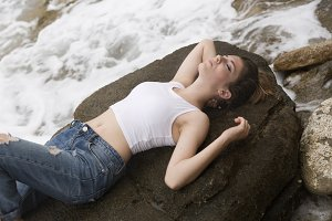 Teenage girl lying on the rocks