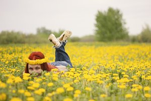 A girl looks out from under the flowers, lying on a flower field