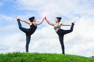 two woman practicing yoga time