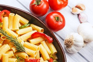 Close-up view of bowl with vegetable pasta served on table with fresh tomatoes and garlic.