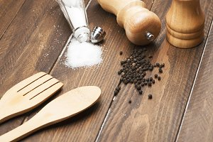 Close-up of salt and pepper next to fork and wooden spoon on wooden table.