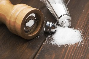 Close-up shot of pair of wooden salts and pepper next to a napkin on wooden table.