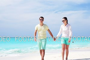 Young couple on white beach during summer vacation. Happy family enjoy their honeymoon. SLOW MOTION VIDEO.