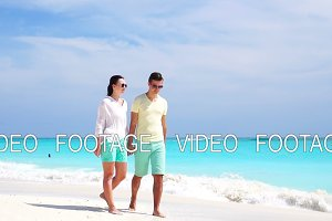Young couple on white beach during summer vacation. Happy lovers enjoy their honeymoon. SLOW MOTION VIDEO.