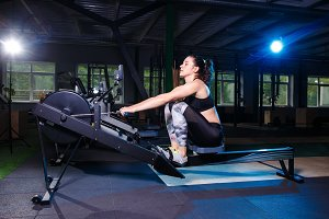 Young strong girl doing an exercise on a rowing machine. For training cardio arms, back. Sporting concepts