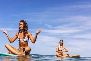 Beautiful girls with surf in ocean.