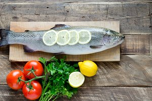 Arcoiris trout with parsley, lemon and tomatoes on wooden board