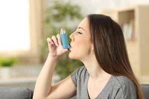 Asthmatic woman using an inhaler