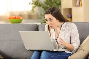 Amazed woman reading on line news