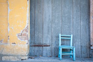 blue wooden chair in front of house